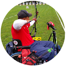 Man in wheelchair shooting with bow and arrow